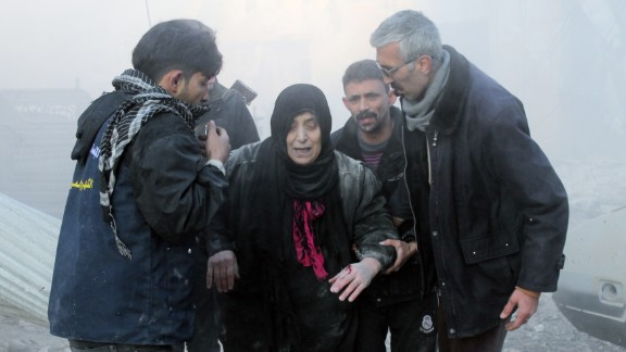 Syrians help a wounded woman following airstrikes on a rebel area in Aleppo on December 15.