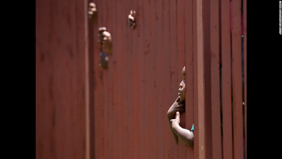 <strong>December 13:</strong> A young boy looks through a fence as he waits in line with thousands of people hoping to board a bus that will take them to view Mandela's body in Pretoria, South Africa.