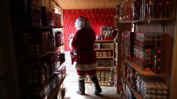 A staff member dressed as Santa Claus walks out to greet customers at the Santa's Place shop in Melbourne on December 16.