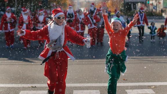 Revelers dressed as Santa Claus run under fake snow during a mini-marathon in Madrid on December 14.