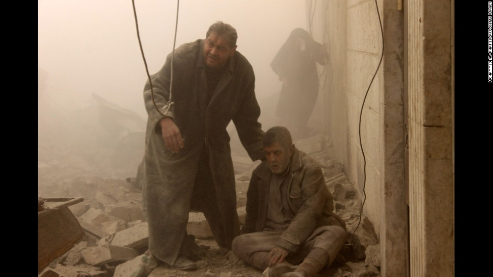 A man sits on the ground after the airstrike in Aleppo on December 17.