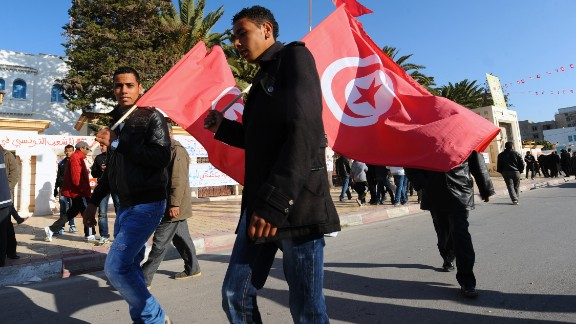 Men wave the national flag to mark the anniversary of the uprising.
