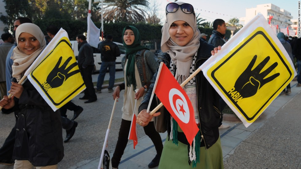"Tunisian girls carry flags showing the symbol known as ""Rabaa,"" which means four in Arabic, remembering those killed in the crackdown on the <a href=""http://cnn.com/2013/08/14/world/meast/egypt-protests/"">Rabaa al-Adawiya protest camp</a> in Cairo, Egypt, earlier in the year."