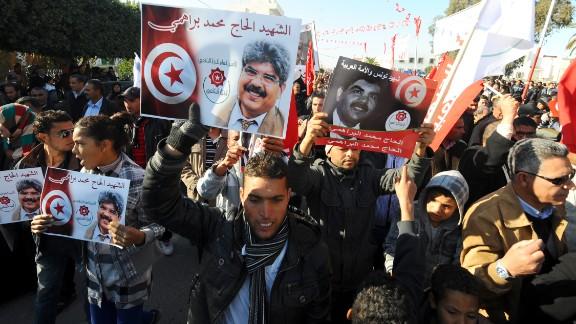 Tunisians carry portraits of assassinated opposition figure Mohamed Brahmi.