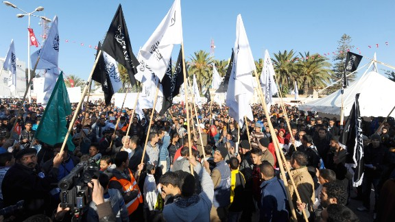 Members of Tunisian Islamist party Hizb-Ut-Tahrir hold islamist flags as they gather to mark the third anniversary of the uprising that toppled deposed president Zine El Abidine Ben Ali in Sidi Bouzid's Mohamed Bouazizi square on December 17, 2013.