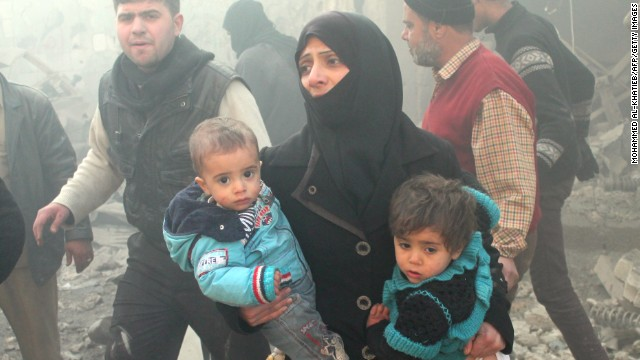 A Syrian woman carries children following airstrikes on Aleppo.