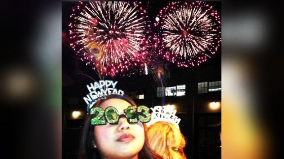 """This photo was taken outside of a waterfront restaurant in San Francisco. """"I am so lucky that my friend Anthony was able to capture not one but TWO fireworks in the background,"""" says Callyan, pictured in the glasses."""