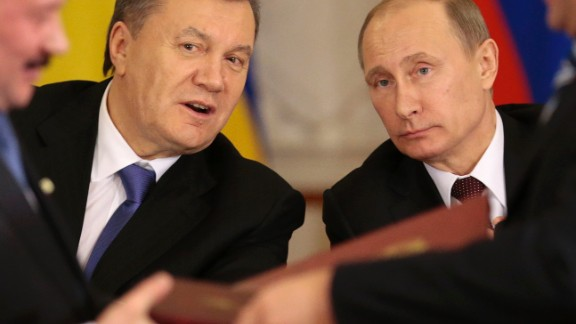 Russian President Vladimir Putin, right, and his Ukrainian counterpart Viktor Yanukovych, left, react after signing an agreement in Moscow on Tuesday, Dec. 17, 2013.