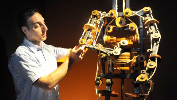"""Massimo Ingrosso inspects the complete mechanism of a robot at a 2009 Leonardo da Vinci exhibition at which the famed inventor's creations, including a 1495 """"automaton,"""" were brought to life."""