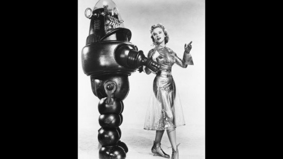 """American actress Anne Francis as Altaira 'Alta' Morbius poses with Robby the Robot in a promotional portrait for """"Forbidden Planet"""" in 1956."""