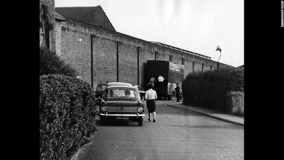People walk around Wandsworth Prison the day after Biggs escaped with three other prisoners in 1965. Biggs made his escape by jumping through a hole in the roof of the furniture van shown here, onto mattresses, and then out of the back of the van into a waiting car.