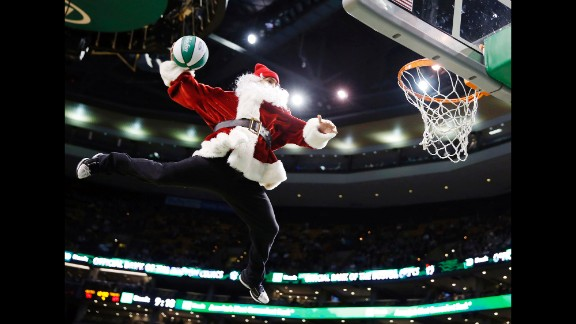 A performer in a Santa Claus costume dunks the ball during a timeout in the fourth quarter of an NBA basketball game between the Boston Celtics and the Minnesota Timberwolves in Boston on Monday, December 16.