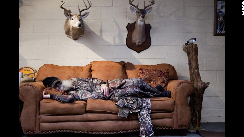 Si takes one of his daily naps, surrounded by some Robertson family trophies.