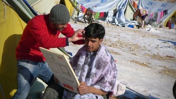 A Syrian refugee gets his hair cut at the  Shuhada Camp.