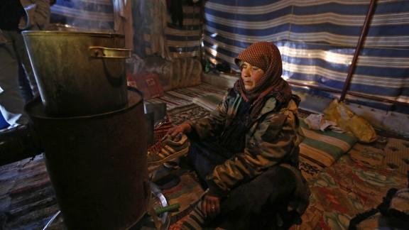 Syrian refugee Mariam al-Hamed burns an old shoe for warmth inside her tent at a refugee camp near Baalbek, Lebanon.