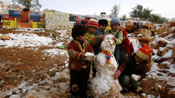 Young refugees build a snowman following a storm in Baaloul on December 12.