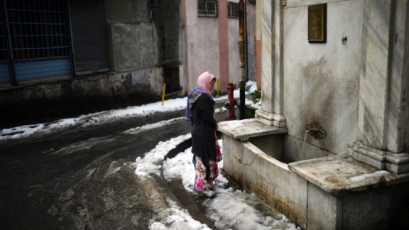 A Syrian woman stands in front of a fountain in Istanbul, Turkey. The recent snowfall brought more misery to refugees in Turkey, who are facing an increasing shortage of supplies.