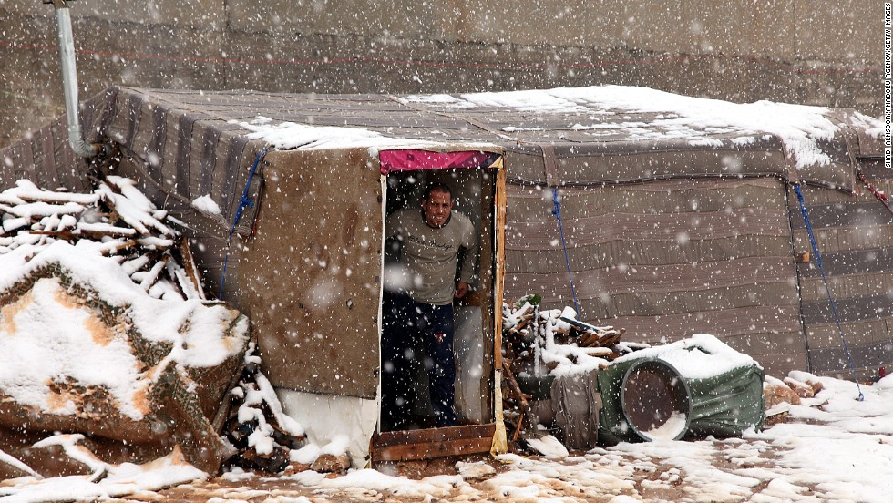 A Syrian refugee looks out of his makeshift tent during a snowstorm in Amman, Jordan.