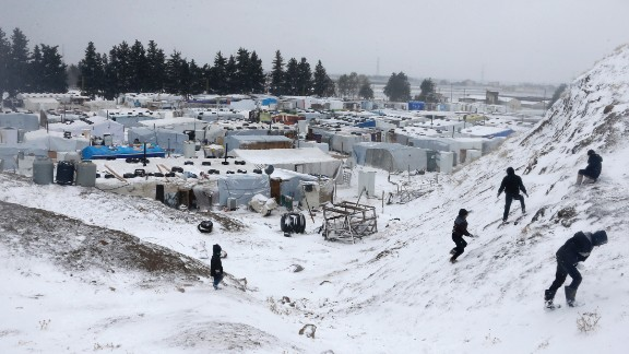 Syrian refugees go out in the snow during a winter storm on December 11 in the Lebanese town of Zahle.