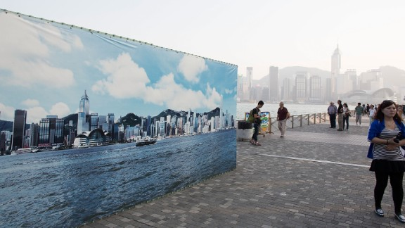 A tourist walks past a billboard featuring a backdrop of the city skyline with a clear sky on October 25 in Hong Kong.