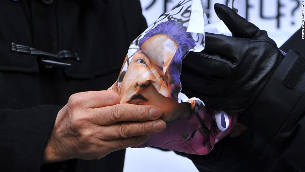 North Korean defectors crumple a caricature of Kim during a protest in Seoul on December 17.