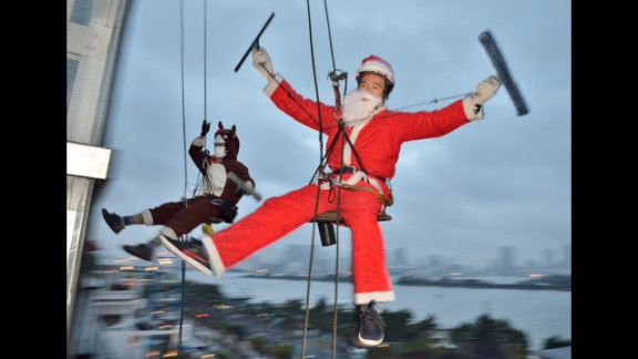 Workers wearing Santa Claus and reindeer costumes clean windows outside of a 100-foot-tall shopping mall at promotional event in Tokyo on December 19.