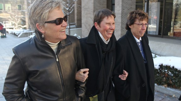 Plaintiffs Laurie Wood, left, and Kody Partridge, center, walk with attorney Peggy Tomsic on December 4, 2013, after a judge heard arguments challenging Utah