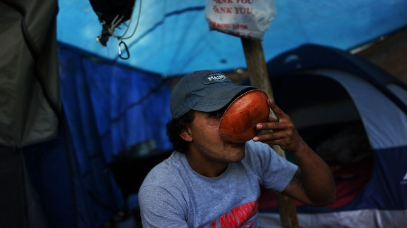 A homeless person takes a drink outside of the tent encampment where he lives in Waterbury, Connecticut.