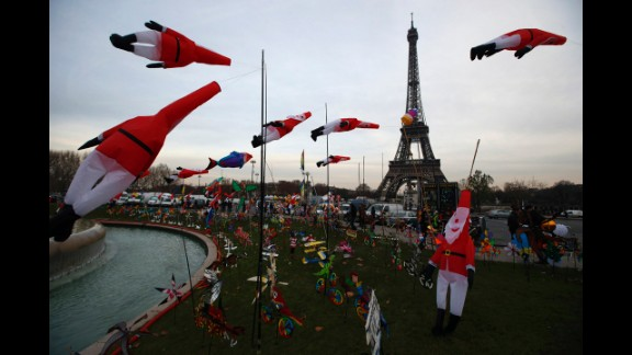 Kites in the shape of Santa Claus glide in the wind as part of an exhibition next to the Eiffel Tower in Paris on Tuesday, December 17.