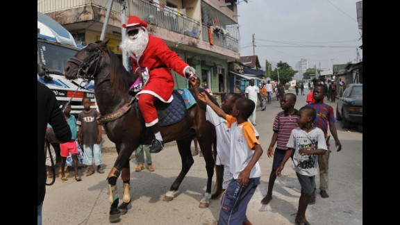 A man wearing a Santa Claus costume rides a horse and distributes gifts to children in a street of Abidjan, Ivory Coast, on December 20.