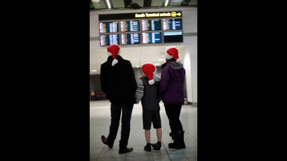 Andy, Harvey and Dianne Thorn look at the arrivals board at Gatwick airport on December 20 in London. Large numbers of people are using the transport system to return home or head off on holiday.