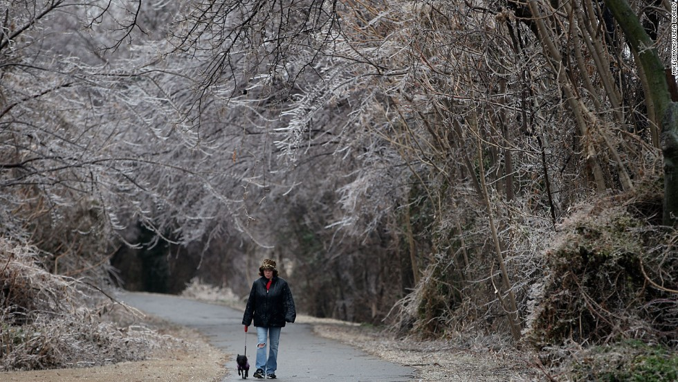 Debra Guthrie walks her dog along a trail surrounded by ice-covered trees in Tulsa, Oklahoma, on December 21.