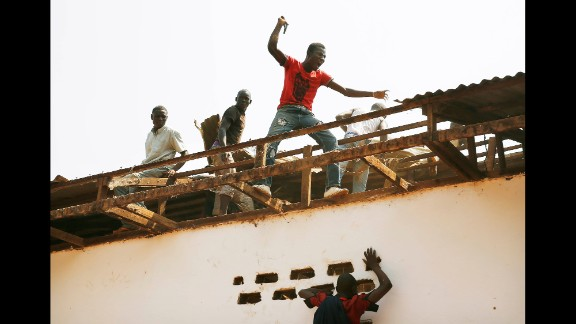 Christian men tear off pieces of the Gobango Mosque in Bangui on December 20.