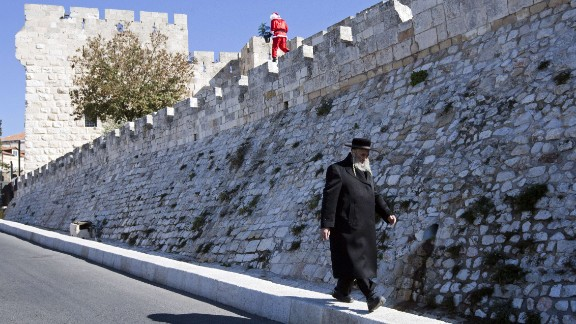 An ultra-Orthodox Jew walks beneath a Palestinian man dressed up as Santa Claus along the walls of Jerusalem's Old City on Sunday, December 22.