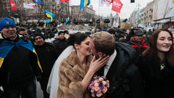 Newlyweds Mikhail and Margarita Nakonechniy kiss in front of barricades on Independence Square in a gesture of support for pro-Europe activists in Kiev, Ukraine, on Saturday, December 21. Protesters have poured into the streets of the Ukrainian capital, angered by their government