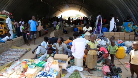 Families seek refuge in U.N. camp warehouse on December 23.