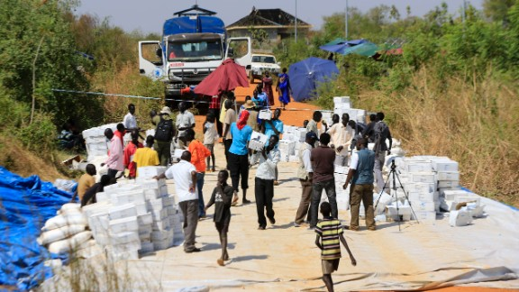 People gather to receive emergency food rations from the World Food Programme at a makeshift camp on December 23.