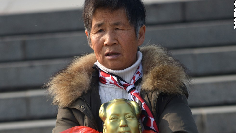 An elderly woman holds a bronze statue of China's former leader Mao Zedong as she makes her way in China's central province of Hunan on December 24, joining others in celebrating Mao's 120th anniversary this week.