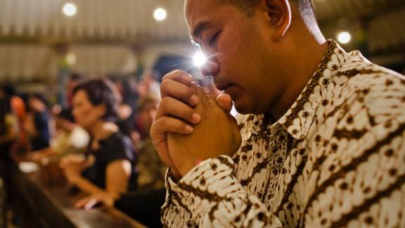 An Indonesian Javanese Christian prays during Christmas Eve Mass in Yogyakarta, Indonesia, on December 24.