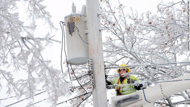 Dave Dora, with Grand Haven Board of Light and Power, works on fallen wires in Lansing, Michigan. on December 23, 2013.