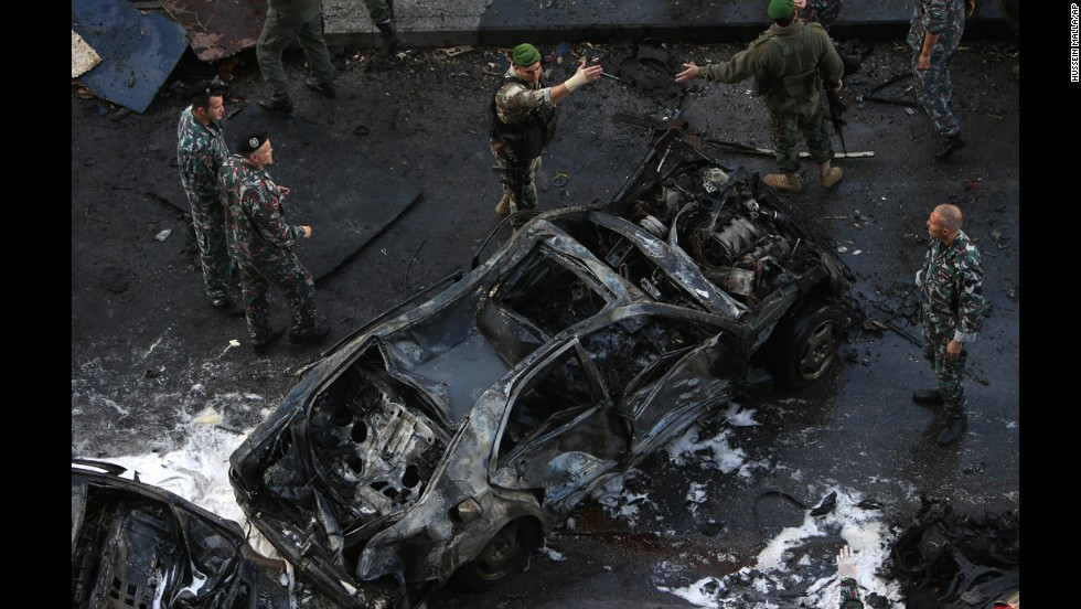 Lebanese soldiers gather around a burned vehicle. Six people were killed in the car bombing and 71 were wounded, Lebanon's health ministry said. Mohamad Chatah, a former Lebanese finance minister and ambassador to the United States, was one of the casualties.