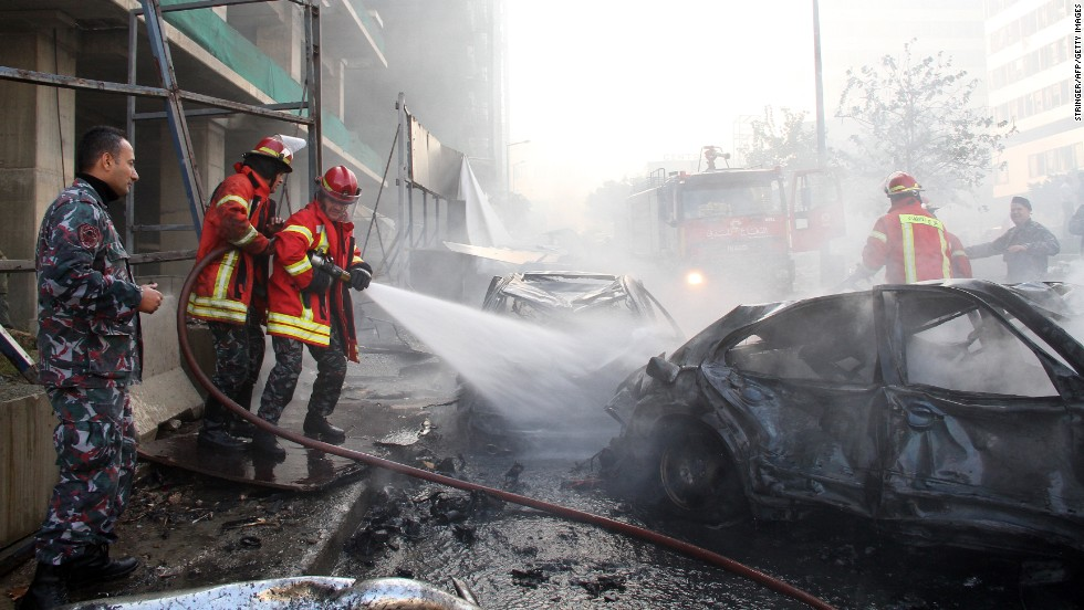 Firefighters douse a burning car after the explosion in central Beirut.