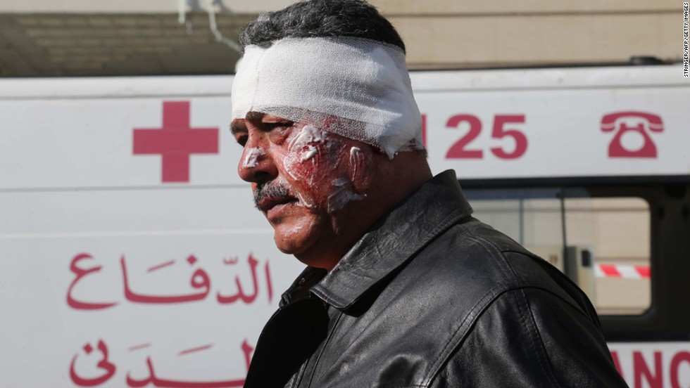 A wounded man walks past a Lebanese civil defense ambulance near the scene.