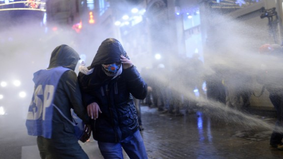 People run away from a water cannon on the Istiklal Avenue on December 27, 2013, during clashes between the Turkish police and protestors. Police blocked hundreds of protesters from gathering in Istanbul's central Taksim Square and pushed them away to the nearby streets. A high-level bribery and corruption investigation involving close government allies has led to a new outpouring of anger against Prime Minister Recep Tayyip Erdogan's government. AFP PHOTO/ BULENT KILICBULENT KILIC/AFP/Getty Images