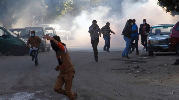 Muslim brotherhood supporters run for cover during clashes with police in Helwan on the outskirts of Cairo on December 27, 2013.