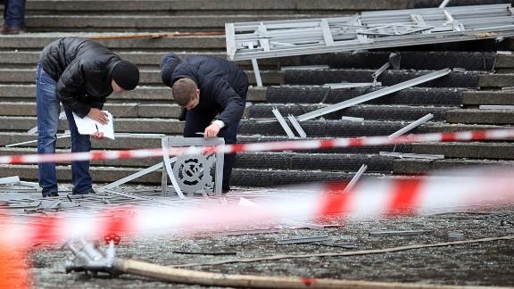 Police investigators inspect debris at the scene of the exlposion.