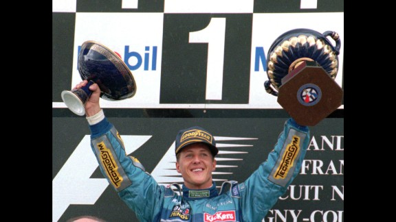 Schumacher holds up the victory trophy, left, and the French Republic President's trophy after winning the French Formula 1 Grand Prix in Magny Cours, France, in 1995.