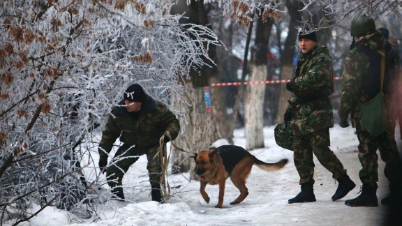 Police officers with a sniffing dog examine territory around the site of a trolleybus explosion in Volgograd, Russia on Monday December 30.