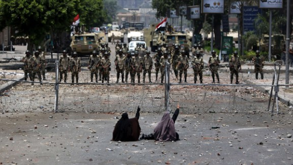 Two veiled Egyptian women, supporters of Mohamed Morsy, sit in front of police standing behind barbed wire fencing that blocks the access to the headquarters of the Republican Guard in Cairo on July 8, 2013.