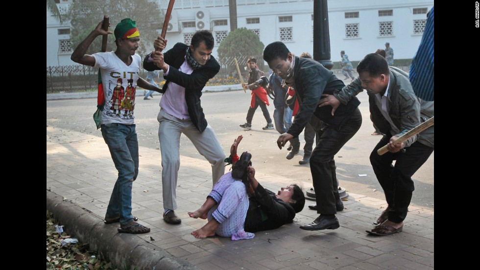 <strong>December 29: </strong>Supporters of the ruling Bangladesh Awami League beat a lawmaker and supporter of the main opposition Bangladesh Nationalist Party during a protest in Dhaka, Bangladesh.